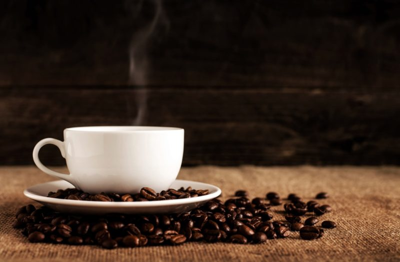 close up of a cup of coffee and beans
